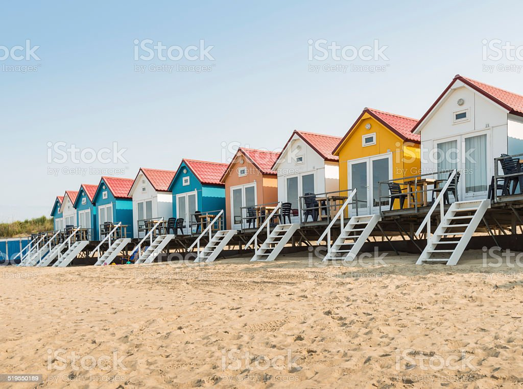Row of colorful beach huts in the sand stock photo