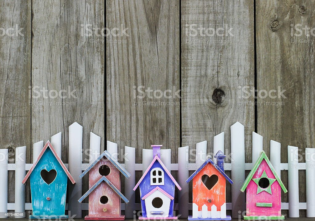 Row of colorful birdhouses by white picket fence stock photo