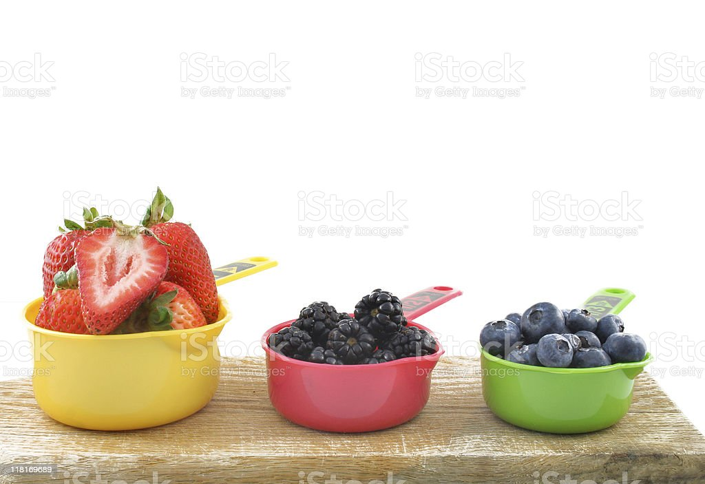 A row of colorful cups of fresh berries on a wooden plank stock photo