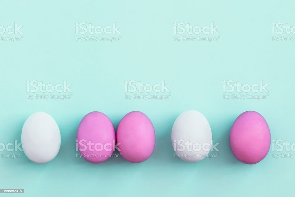 Row of colorful Easter eggs on blue background stock photo