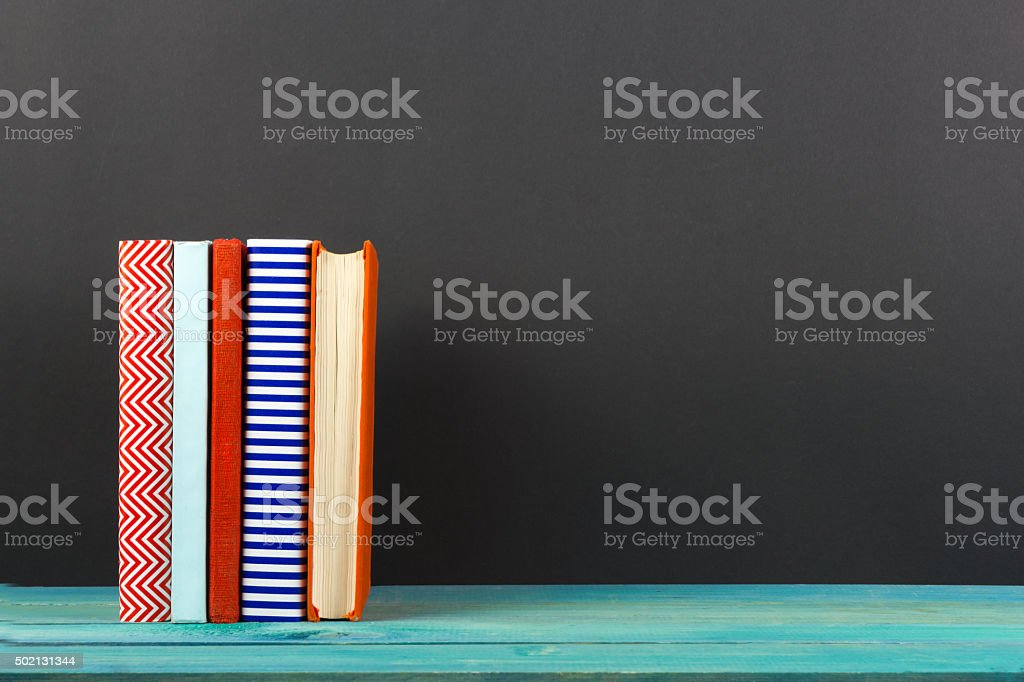 Row of colorful hardback books, open book on black background stock photo