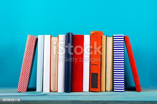 istock Row of colorful hardback books, open book on blue background 504649118