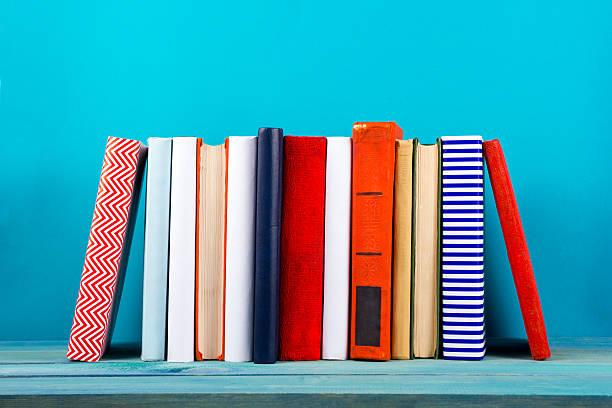 Fila de colorido y de tapa dura libros, libro abierto en fondo azul - foto de stock