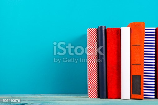 istock Row of colorful hardback books, open book on blue background 505410976