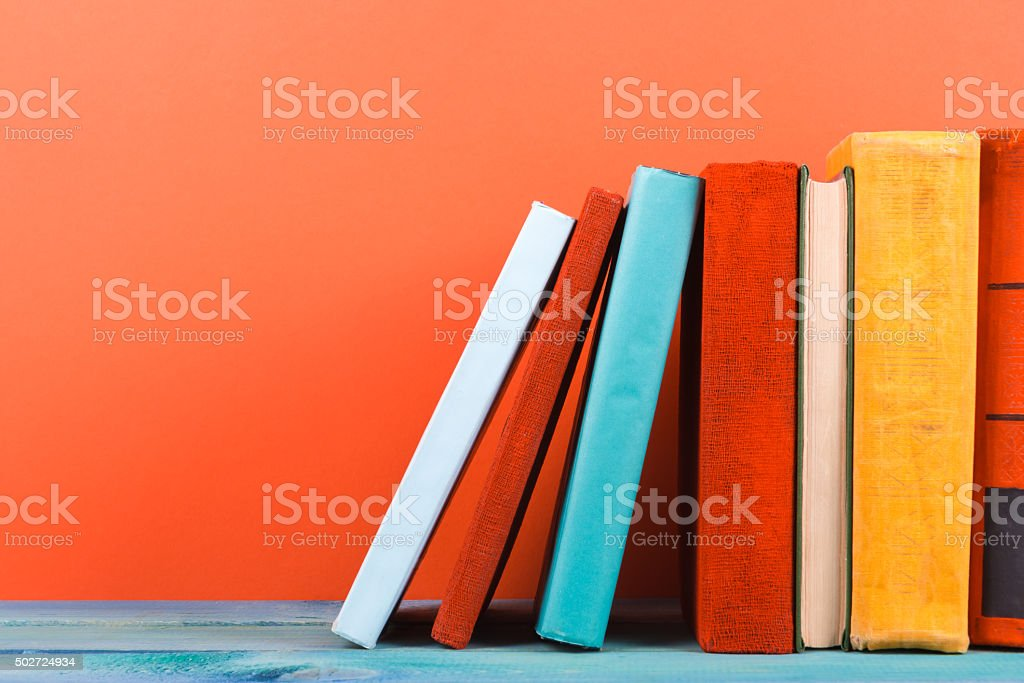 Row of colorful hardback books, open book on red background stock photo