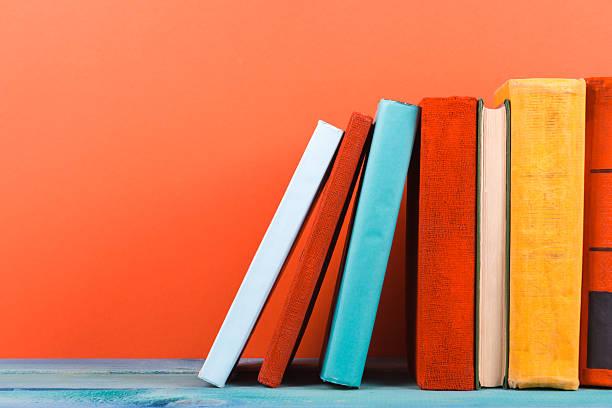 Fila de colorido y de tapa dura libros, abrir libro sobre fondo rojo - foto de stock