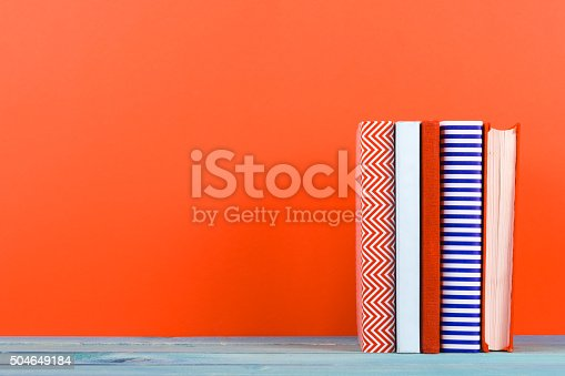 istock Row of colorful hardback books, open book on red background 504649184