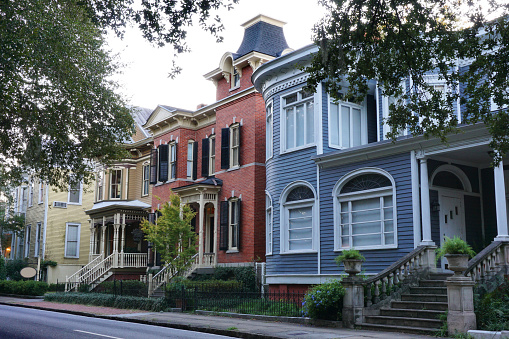 Exterior view of yellow, red, blue and brown, Victorian houses in downtown Savannah Georgia