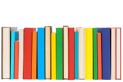Row of colorful library books isolated on white background .