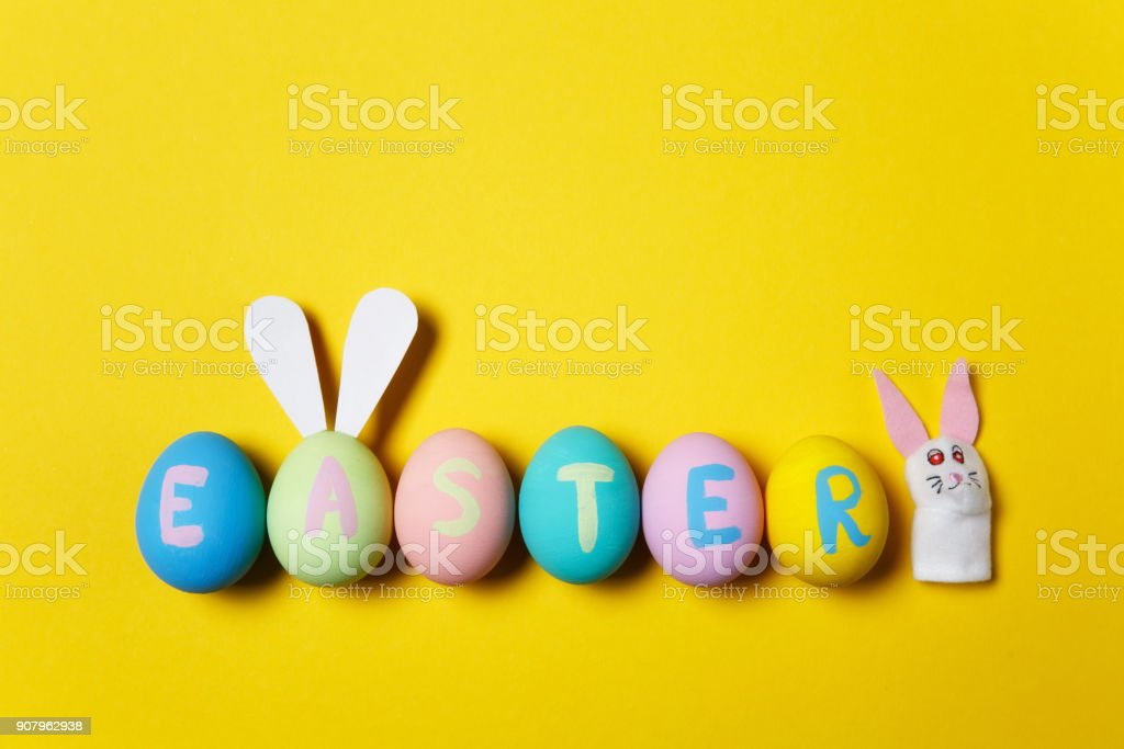 Row of colorful pastel monophonic painted Easter eggs with inscription Easter, fun bunny ears on egg, white rabbit on yellow background. Copy space for advertisement. With place for text. Top view. stock photo