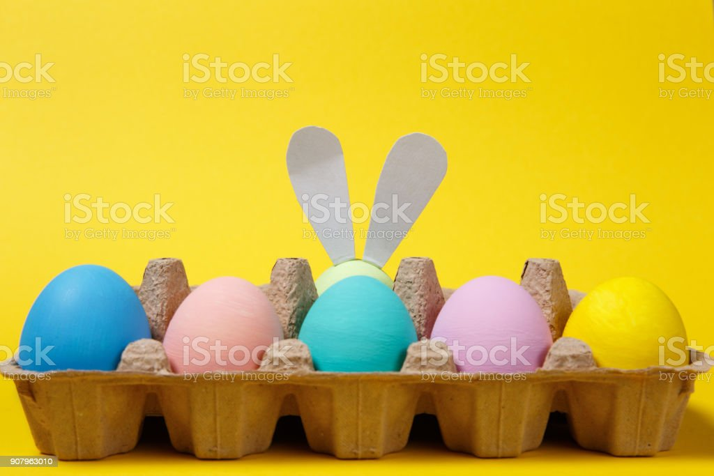 Row of colorful pastel monophonic painted Easter eggs with fun bunny ears in cardboard tray on yellow background for card. Happy Easter concept. Copy space for advertisement. With place for text. stock photo