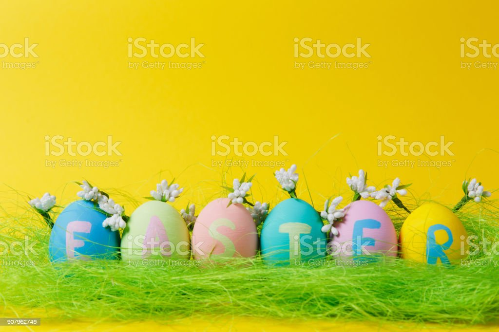 Row of colorful pastel painted Easter eggs with inscription Easter in green grass, white flowers lilies of valley isolated on yellow background. Copy space for advertisement. With place for text. stock photo