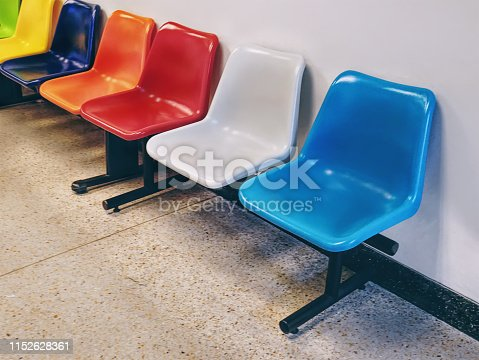 istock Row of Colorful Plastic Chairs Against White Wall 1152628361