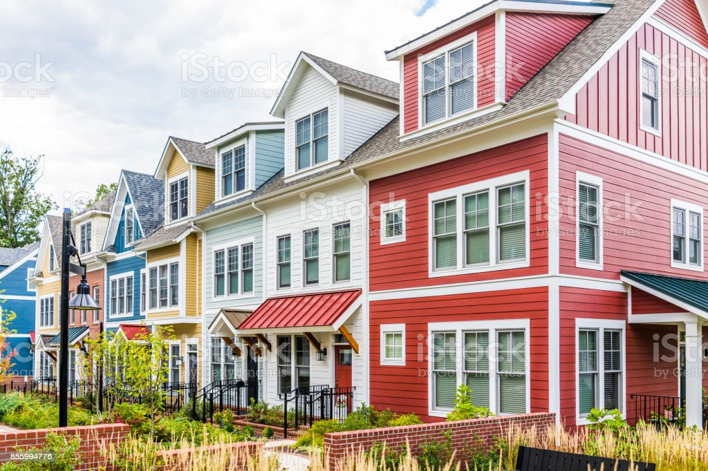 Row of colorful, red, yellow, blue, white, green painted residential townhouses, homes, houses with brick patio gardens in summer stock photo