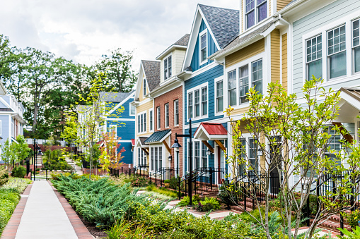 istock Row of colorful, red, yellow, blue, white, green painted residential townhouses, homes, houses with brick patio gardens in summer 857082594