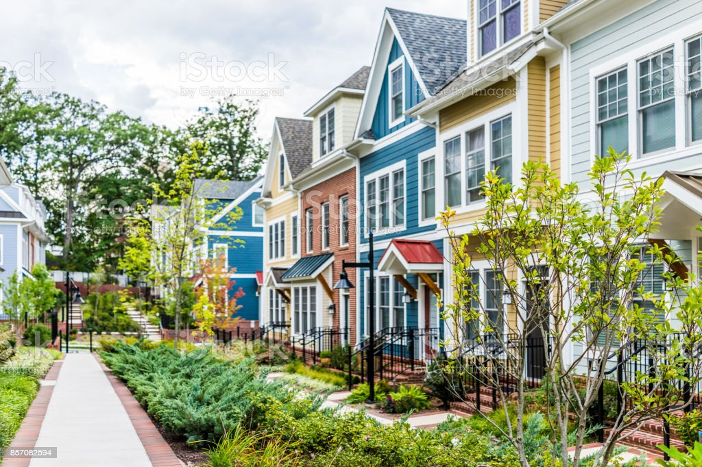 Row of colorful, red, yellow, blue, white, green painted residential townhouses, homes, houses with brick patio gardens in summer - foto stock