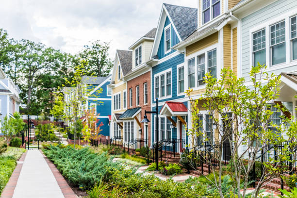 row of colorful, red, yellow, blue, white, green painted residential townhouses, homes, houses with brick patio gardens in summer - terraced houses stock photos and pictures