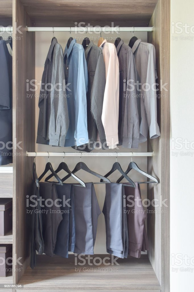 Row Of Colorful Shirts And Pants Hanging In Wooden Wardrobe Royalty Free  Stock Photo