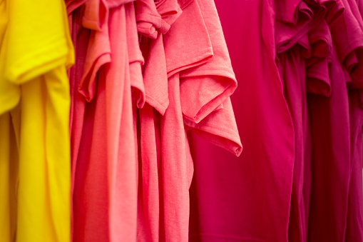 Row of Colorful T-Shirts Hanging on Rack, Close-Up