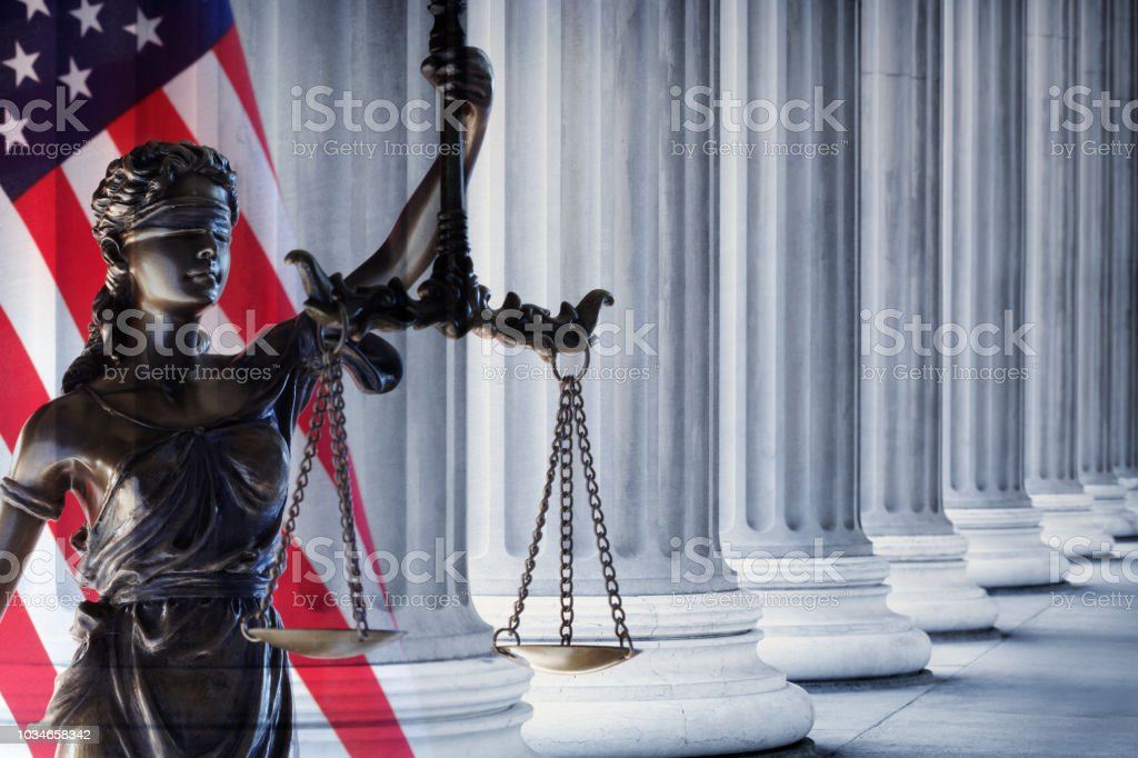 Row Of Columns And Lady Justice Statue In Front Of American Flag stock photo