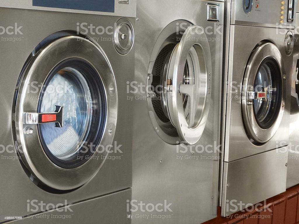 Row Of Commercial Washing Machines In Public Laundromat