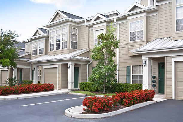 row of condominiums with french windows - pauwenkers stockfoto's en -beelden