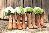 Cowboy boots and bouquets are lined up by a grey barn at a country theme wedding
