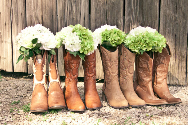 row of cowboy boots and bouquets at a country theme wedding - west direction stock pictures, royalty-free photos & images