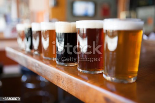 istock Row of different beers in glasses on a wooden bar 495306979