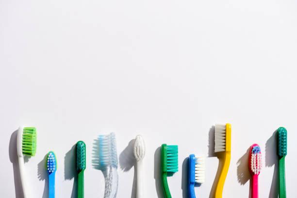 reihe von verschiedenen zahnbürsten auf weiß mit textfreiraum - zähne putzen stock-fotos und bilder