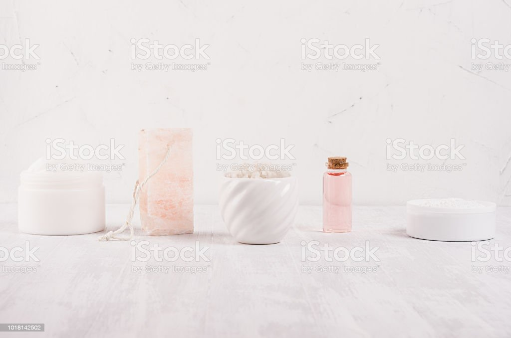 Row of different white and pink spa products for body and skin care...