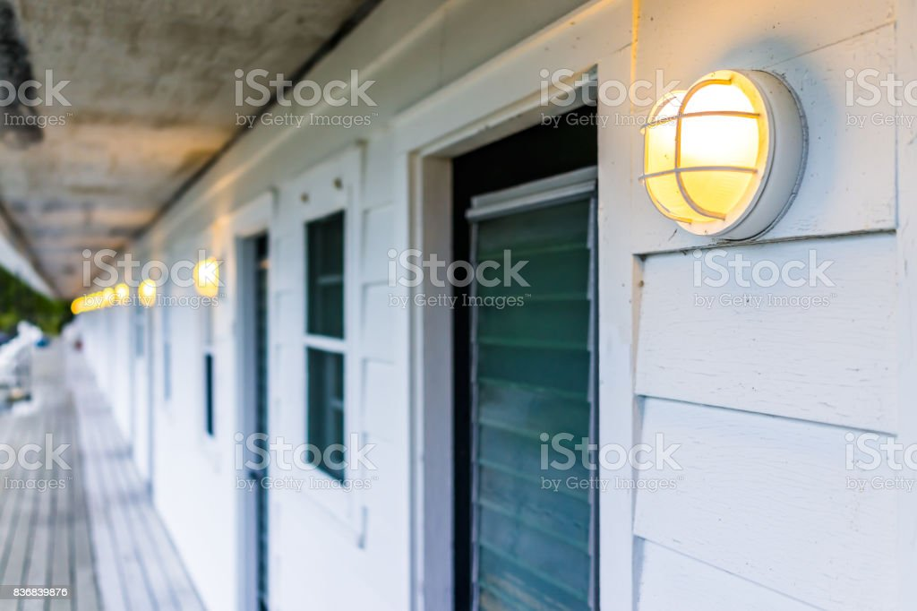 Row of doors outside with illuminated lights lamps in evening stock photo