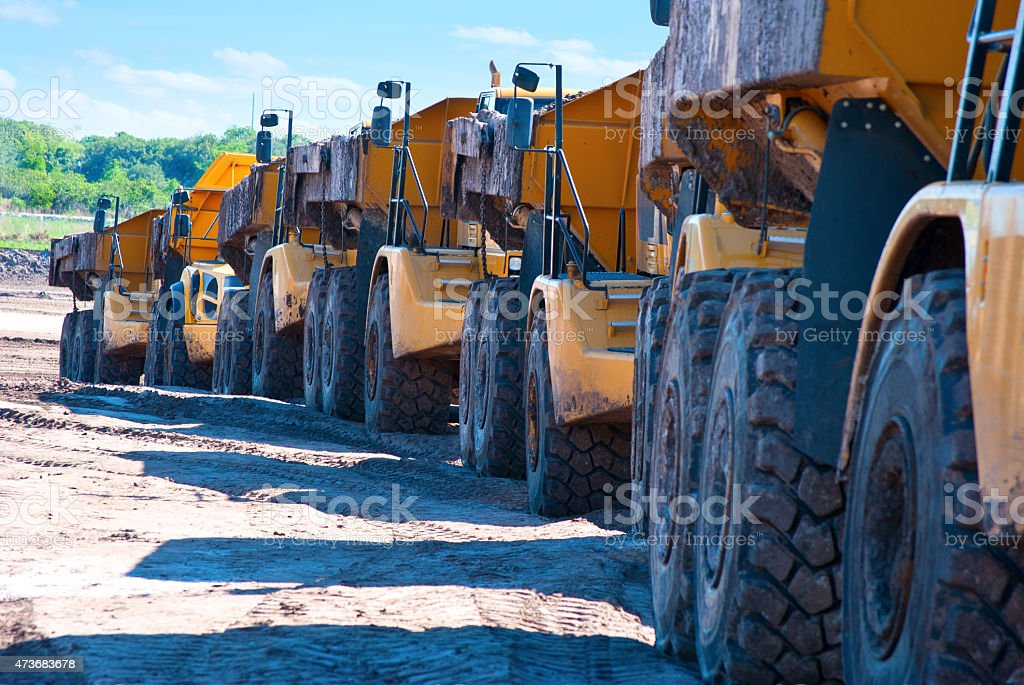 Row of dump trucks driving through construction zone stock photo