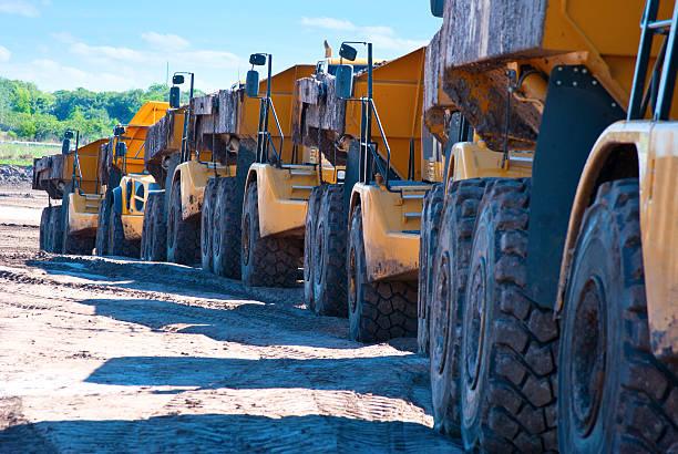Row of dump trucks driving through construction zone stock photo