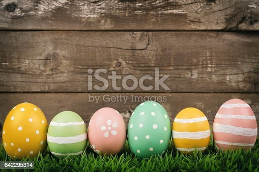 istock Row of Easter eggs on grass over rustic wood 642295314
