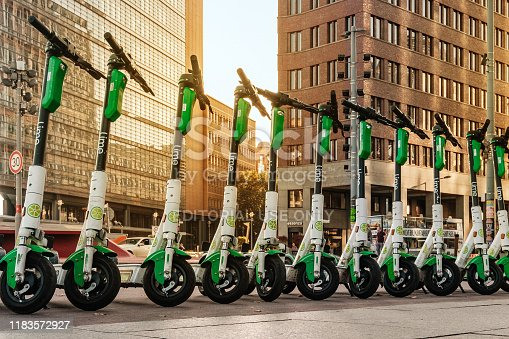 Berlin, Germany - October, 2019: Row of electric E scooters , escooter or e-scooter of the company LIME on sidewalk in Berlin