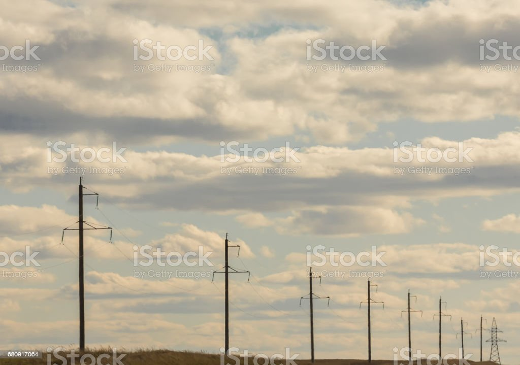 Row of electricity pylons and lines at summer field, sunny day royalty-free stock photo