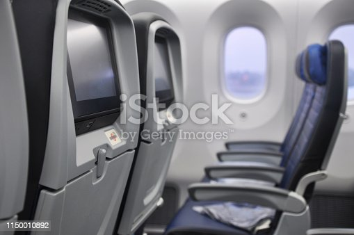 Row of empty blue leather airplane seats and window on a Boeing 787 Dreamliner