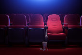 Interior of empty dark cinema with rows of red seats with cup holders and popcorn. Concept of entertainment. 3d rendering toned image