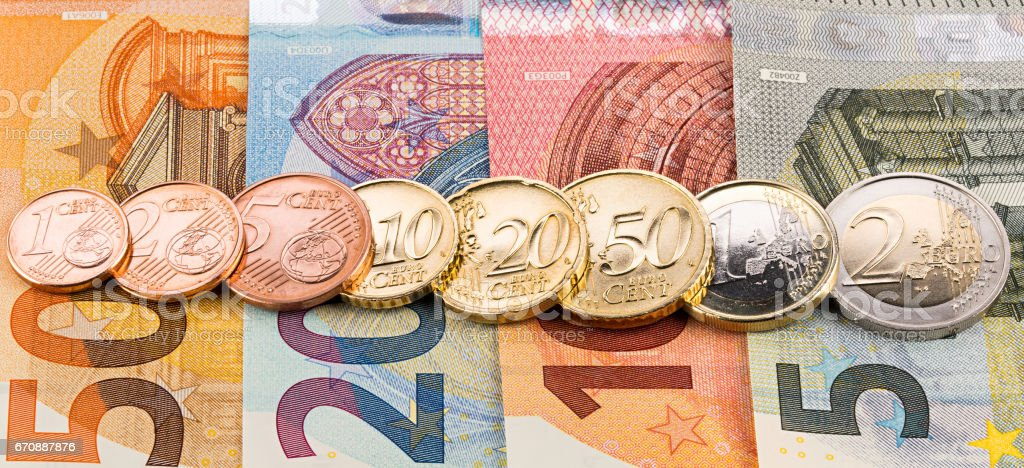 row of euro cent coins on bank notes stock photo