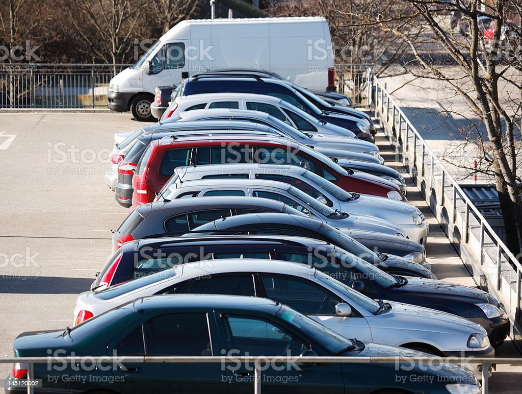row of european cars in parking lot stock photo