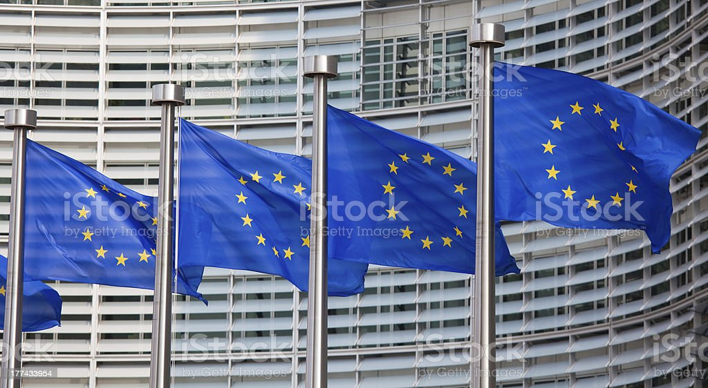 Row of European Union flags waving in the wind European flags in front of the Berlaymont building, headquarters of the European commission in Brussels. Authority Stock Photo