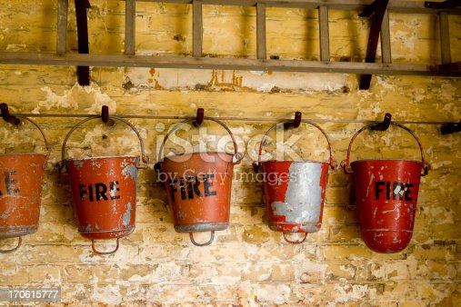A row of old damaged fire buckets in a dark room. The handles on the bottoms are to make it easier to hurl the contents over flames.