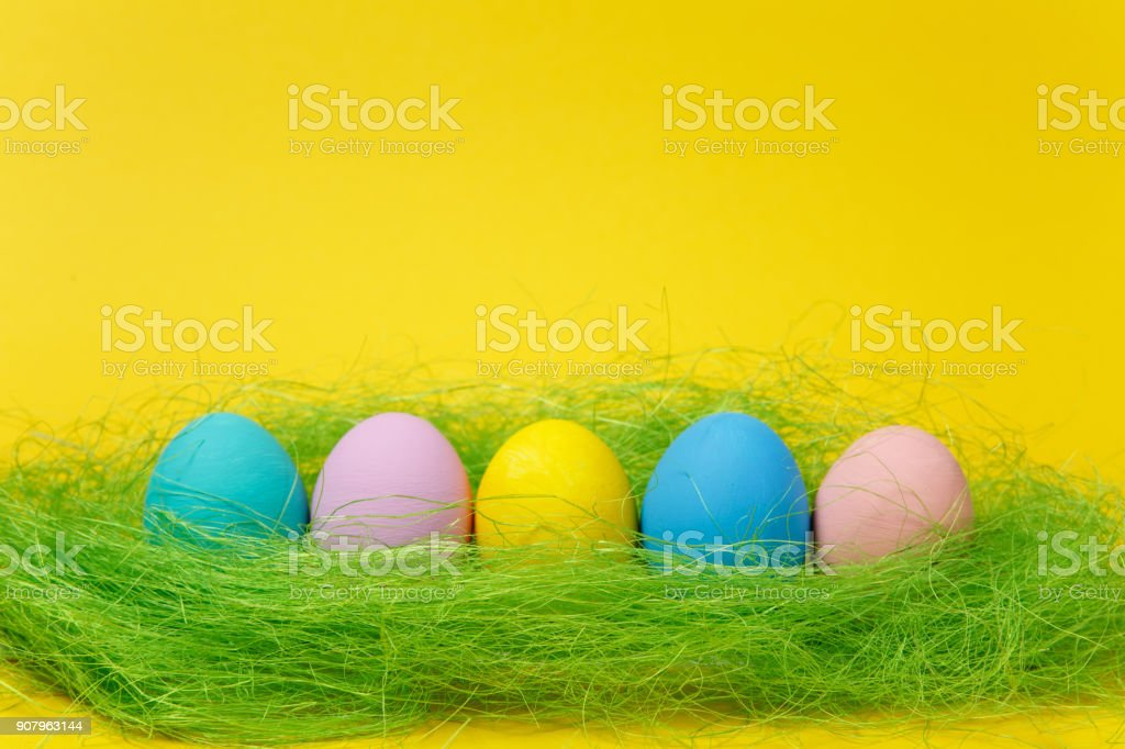Row of five colorful pastel monophonic painted Easter eggs in green grass on yellow background for card or postcard. Happy Easter concept. Copy space for advertisement. With place for text. stock photo