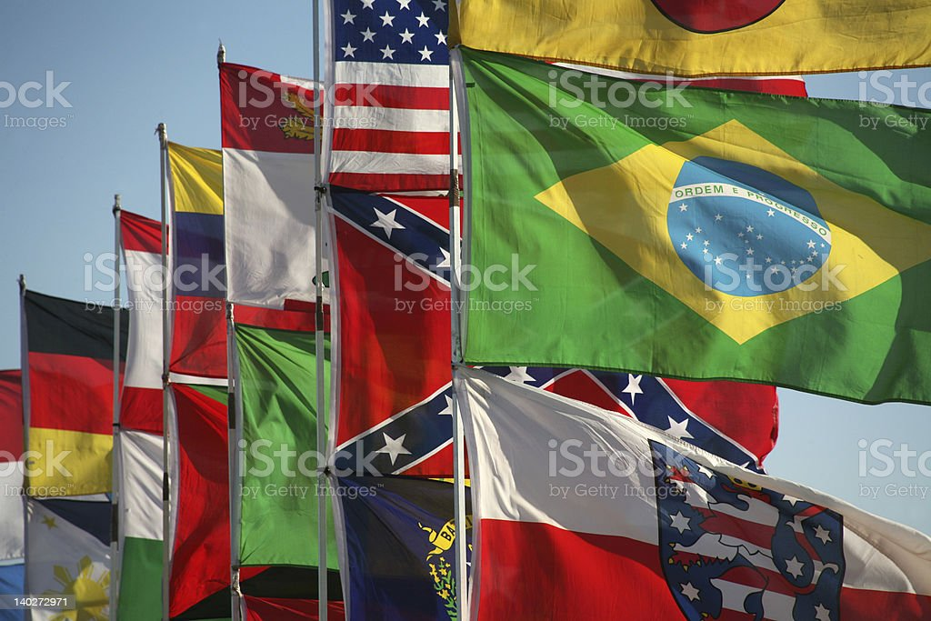 Row of flagpoles with flags of the world flying stock photo