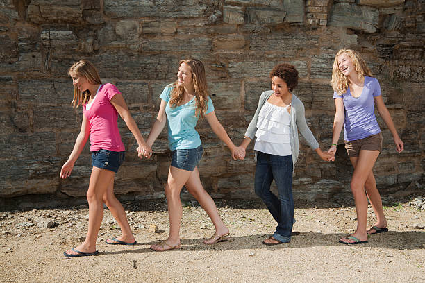 Row of Four Cute Teenager Girl Friends Walking Holding Hands stock photo