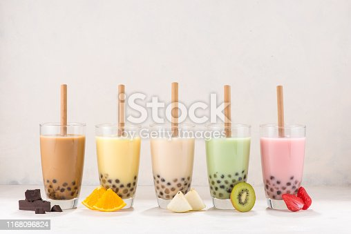Row of fresh boba bubble tea glasses with straw on white background. Slices of fruity ingredients with delicious glasses of a summer refreshment.