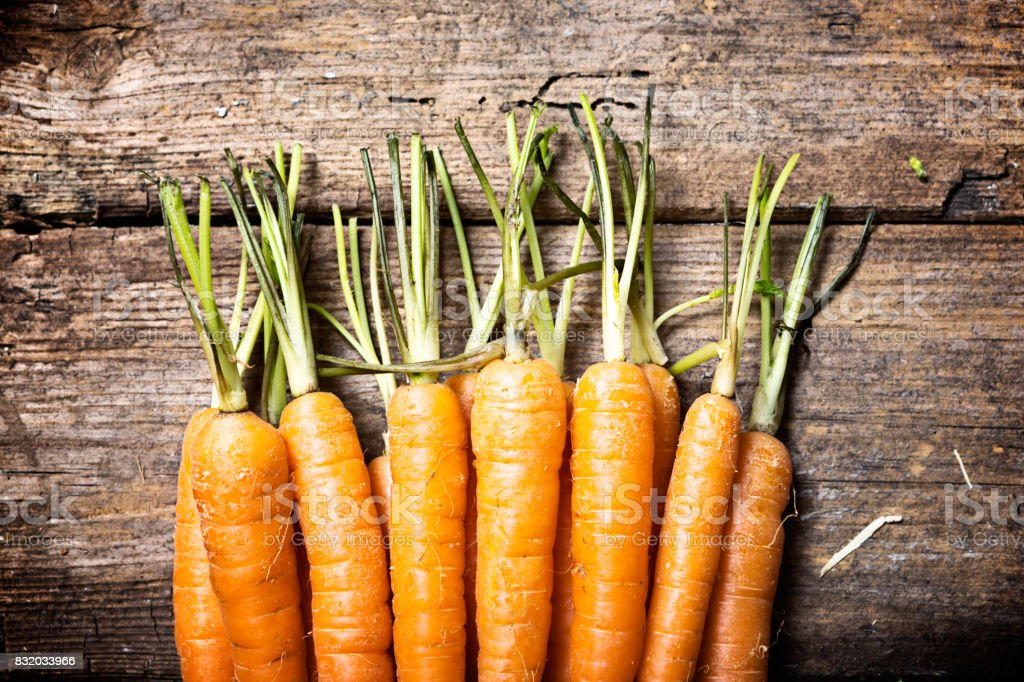 Row of fresh, trimmed carrots on worn wooden background stock photo