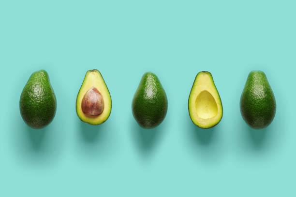 fileira de totalidades e de metades frescos do abacate orgânico com as sementes no centro no backgrond azul. vista superior - abacate - fotografias e filmes do acervo