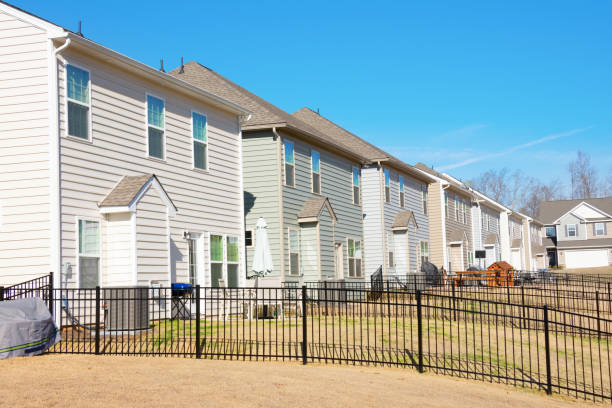 Row of generic houses from backyard view in a southeast U.S. suburb on a beautiful blue sky day stock photo